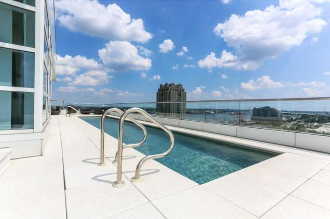 Full renovation of two floor penthouse in Center City, Philadelphia. White, large format tile, brushed brass staircase, rooftop swimming pool, and an interior water feature are among the improvements.